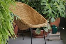 Vasos de barro, jardim vertical e futon transformam o terraço em um gostoso cantinho verde